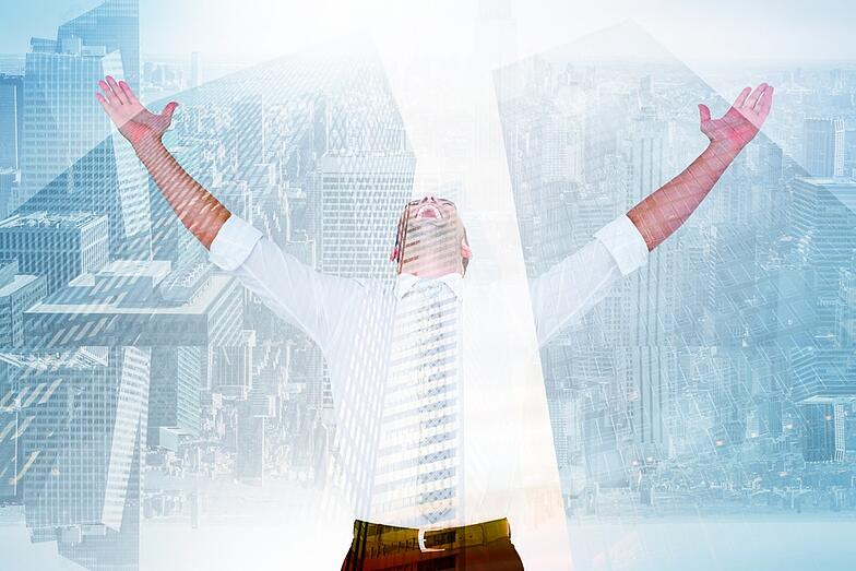 Handsome businessman cheering with arms up against low angle view of skyscrapers.jpeg